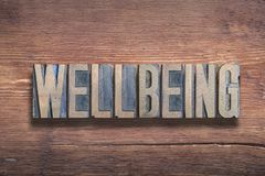 Wellbeing word wood. Wellbeing word combined on vintage varnished wooden surface stock photography