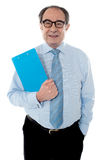 Welldress corporate person holding document. Corporate person holding document and smiling at camera Stock Photography
