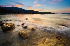Welle auf dem Strand mit Sonnenuntergang stockfoto