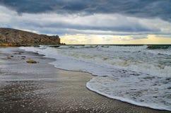Welle der Brandung auf einem sandigen Strand im wolkigen Wetter Krim, Sudak Lizenzfreie Stockfotografie