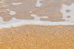 Welle des Wassers auf freiem sandigem Strand Stockbilder