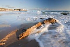Welle, die über einem Felsen am Sonnenuntergang sich wäscht Stockbild