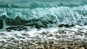 Welle, die auf dem pebbels Strand zerquetscht Lizenzfreies Stockfoto