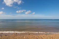 Welle, die auf dem Sandstrand spritzt Stockfotografie