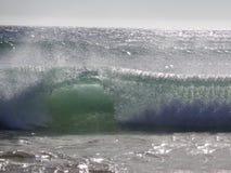 Welle, die auf dem Strand bricht stockfotos