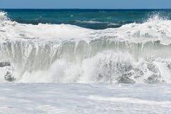 Welle, die auf dem Strand spritzt Lizenzfreie Stockbilder