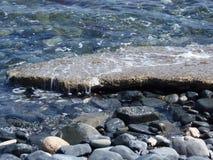 Welle, die auf einem flachen Felsen spritzt Lizenzfreie Stockfotografie