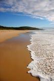 Welle, die auf einem Strand bricht Stockfotos