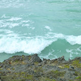 Welle, die auf einer Klippe zusammenstößt Stockbilder