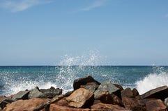 Welle, die auf Felsen spritzt Lizenzfreies Stockbild