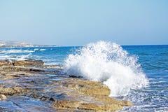 Welle, die auf Felsen spritzt Stockbilder