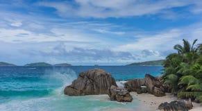 Welle, die auf tropischem Strand des Granitfelsens bricht Stockbild
