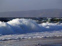 Welle, die auf wildem Strand mit Schaumgummi abbricht stockfotos
