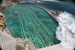 Welle, die ein natürliches Pool mit Schwimmern schlägt Lizenzfreie Stockfotografie