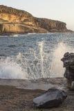 Welle, die am felsigen Ufer spritzt Stockfoto