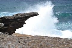 Welle, die gegen die Felsen zusammenstößt Stockbilder