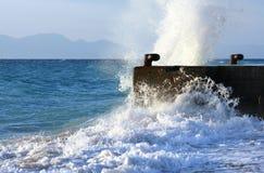 Welle, die gegen Steinverankerungs- bricht Lizenzfreie Stockfotos