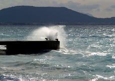 Welle, die gegen Steinverankerungs- bricht Stockfotografie