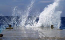 Welle, die gegen Steinverankerungs- bricht Stockbilder