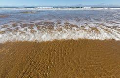 Welle hüllt einen goldenen Sandstrand ein lizenzfreie stockfotografie