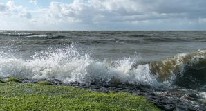 Welle schlägt die Küstenfelsen in Holland während des Sturms Stockfoto