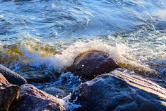 Welle schlägt enormen Stein am Seeufer ein Stockfoto