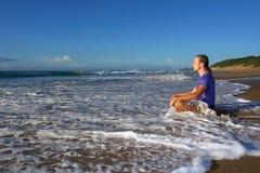 Welle spritzt auf meditierendem jungem Mann stockfotografie