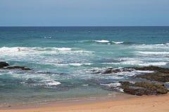 Wellen über Felsen auf dem Strand stockbilder