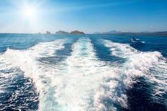 Wellen auf blauem Meer hinter dem Boot Stockfotografie