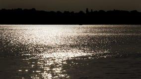 Wellen auf dem Flusswasser auf dem Sonnenuntergang beleuchten stock video