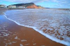 Wellen auf dem sandigen Strand in Sidmouth Stockfotografie
