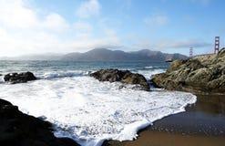 Wellen auf dem Strand durch golden gate bridge lizenzfreie stockfotografie