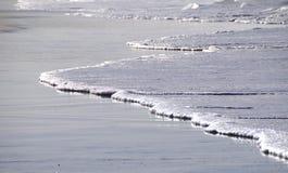 Wellen auf dem Strand im Sonnenlicht Lizenzfreies Stockbild