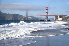 Wellen auf dem Strand mit dem Golden Gate stockfotografie