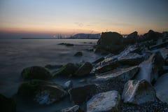 Wellen auf den Felsen bei Sonnenuntergang stockbild