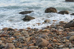 Wellen auf einem felsigen Strand Stockbilder