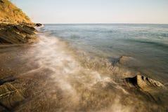 Wellen auf einer Strand-Küstenlinie Stockfotos