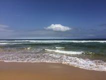 Wellen auf sandigem Strand Stockbild