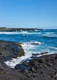 Wellen auf schwarzem vulkanischem Felsen Lizenzfreies Stockfoto