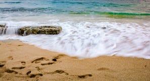 Wellen auf Strand bei Sonnenuntergang lizenzfreie stockbilder