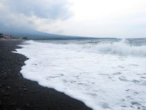 Wellen, Brandung und Gischt, die den sandigen schwarzen vulkanischen Sandstrand von Bali schlagen In Amed ist das Meer ruhig, abe lizenzfreie stockfotos