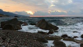 Wellen brechen über Steine bei Sonnenaufgang über Meer stock footage