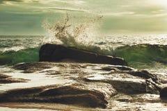 Wellen brechen durch einen Stein lizenzfreie stockfotos