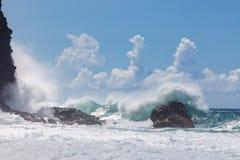 Wellen, brechend auf felsiger, ursprünglicher Küstenlinie unter blauem Himmel mit Lizenzfreie Stockfotografie
