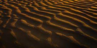Wellen in den Sanddünen bei Sonnenuntergang Lizenzfreies Stockfoto