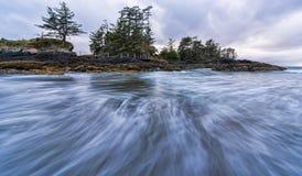 Wellen in der Bewegung und in Baum gefüllter Insel Stockfoto