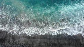 Wellen des Atlantik-Schlages gegen das felsige Ufer, den schwarzen vulkanischen Sand und die Strandansicht von oben Seebrandungst stock video