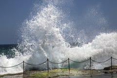 Wellen, die über dem Geländer zum Blockwagen-Loch zusammenstoßen Lizenzfreie Stockbilder