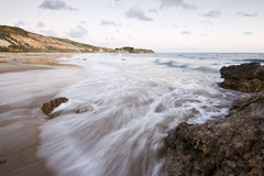 Wellen, die über einem Felsen am Sonnenuntergang sich waschen Lizenzfreie Stockbilder