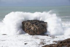 Wellen, die über Felsen brechen Stockbilder